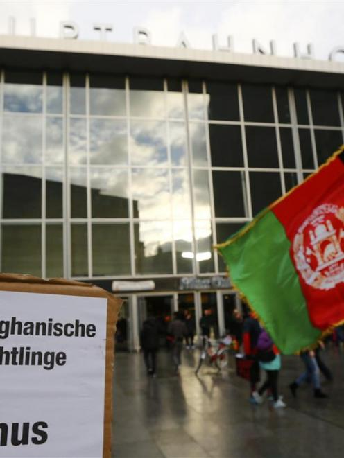 A man holds Afghan flags next to a placard reading ''Afghan refugees against sexism'' outside the...