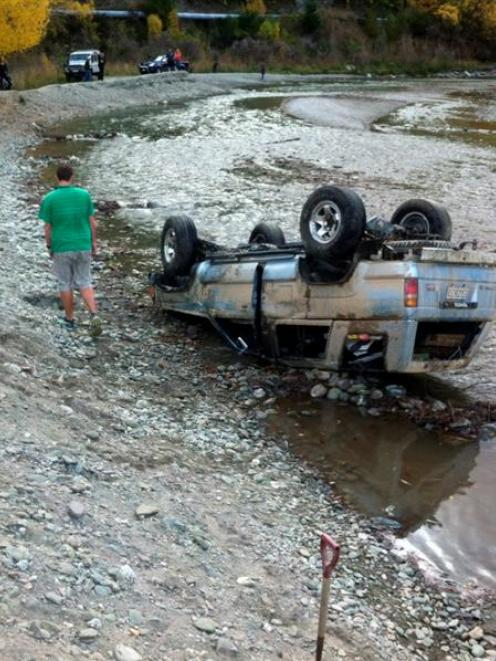 A man inspects the damage to a 4WD on Monday afternoon after the vehicle landed on its roof in...