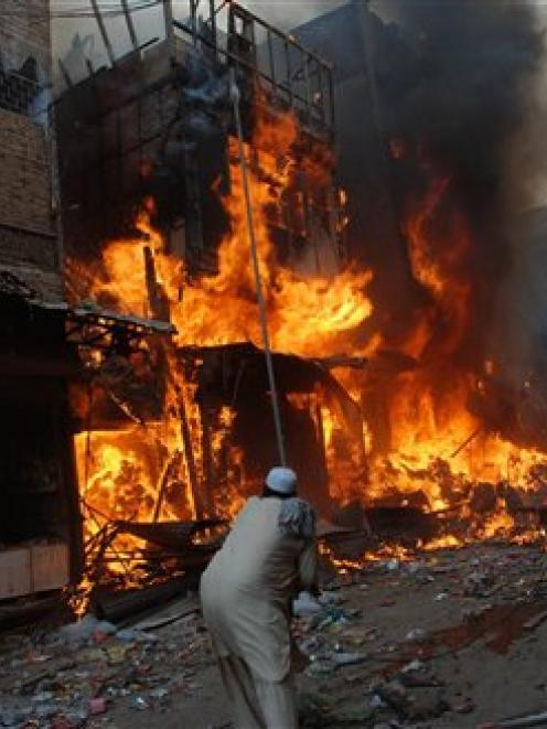A man is seen at the spot of an explosion in Peshawar, Pakistan. A car bomb has torn through a...