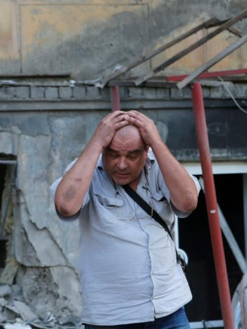 A man reacts as he stands in front of a building damaged by, what locals say, was recent shelling...