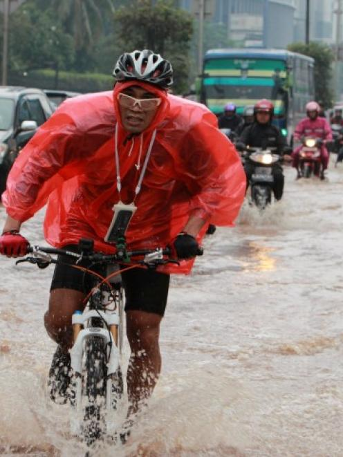 A man rides his bicycle through a flooded street as he heads to work in the business district in...