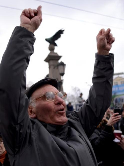 A man shouts slogans as people block the traffic during a protest against high electricity bills...