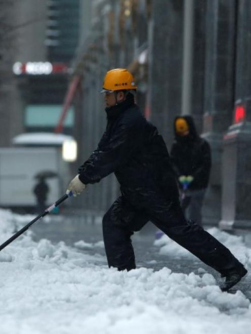 A man shovels snow on Tokyo street. REUTERS/Yuya Shino