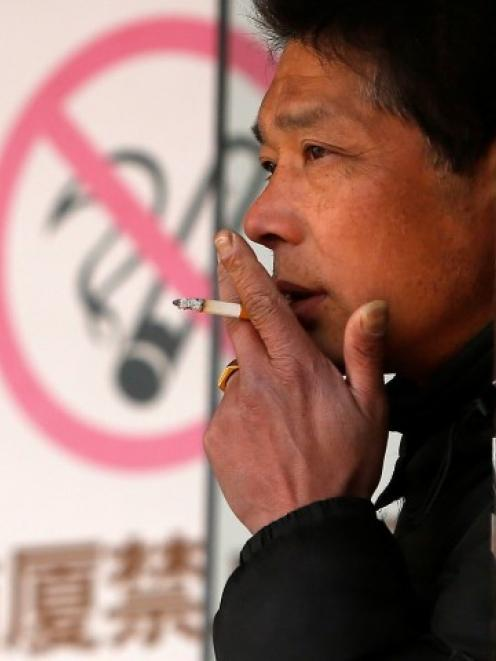 A man smokes in front of a 'no smoking' sign outside a shopping mall in Shanghai. REUTERS/Aly...