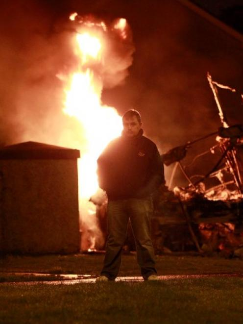 A man stands in front of a burning double-decker bus which was hijacked and set alight by...