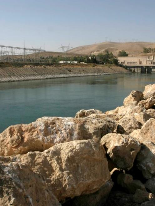 A man stands on the banks of the Mosul Dam on the Tigris River 390km northwest of Baghdad, in...