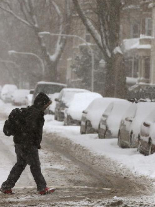 A man walks across a snow-covered street in the Humboldt Park neighbourhood in Chicago. (Photo by...