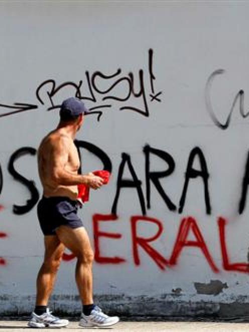 A man walks past graffiti against Portugal's Prime Minister Pedro Passos Coelho on the streets of...