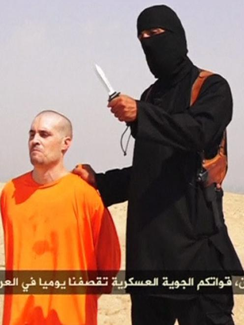 A masked Islamic State militant holding a knife speaks next to man purported to be U.S....