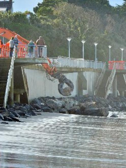 A mechanical arm gently places a large rock from the Blackhead Quarry in front of the St Clair...