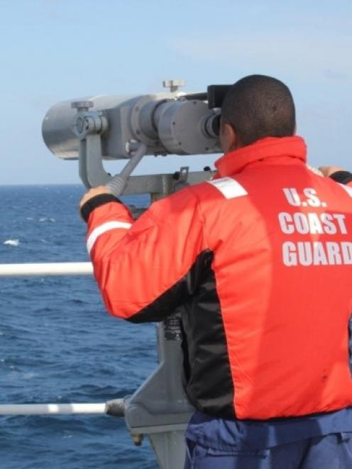 A member of the US Coast Guard Cutter Vigorous searches for the sailing vessel Cheeki Rafiki,...