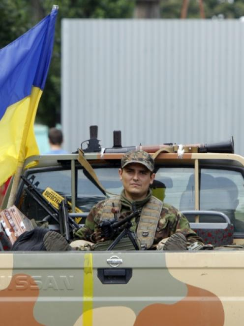 "A member of Ukrainian self-defence battalion ""Donbass"" rides on a pick-up truck during a patrol...."