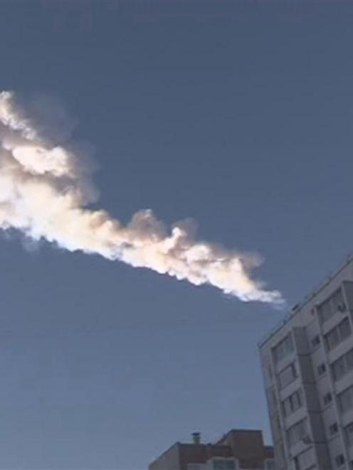 A meteor trail is seen above a residential apartment block in the Urals city of Chelyabinsk. REUTERS