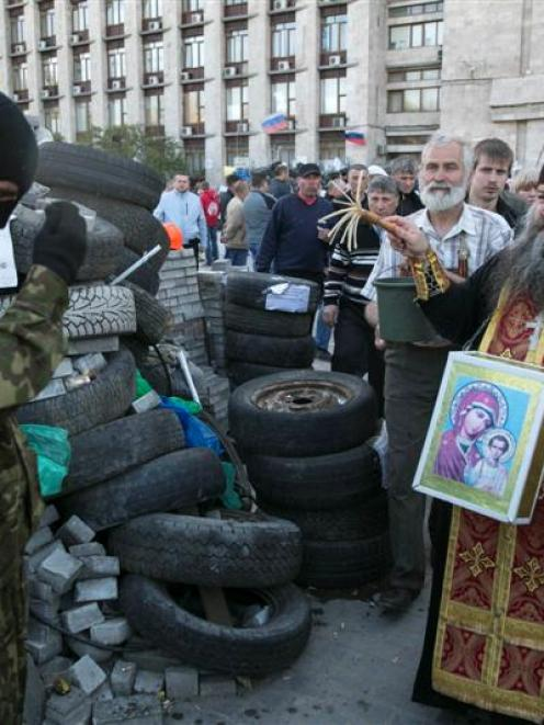 A monk blesses a Pro-Russian activist outside a regional government building in Donetsk, eastern...