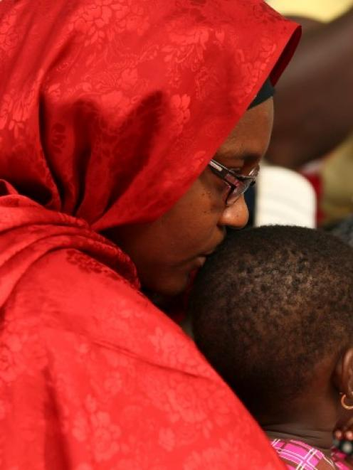 A mother kisses her daughter as they participate in protest demanding the release of the abducted...
