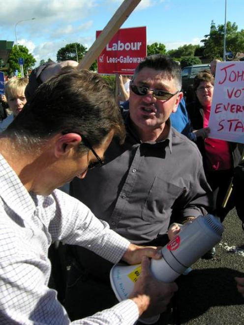 A National supporter tries to forcibly take a megaphone off Labour supporter Wayne Ruscoe at a...