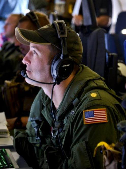 A Naval Flight Officer assigned to Patrol Squadron (VP) 16, monitors his workstation on a P-8A...