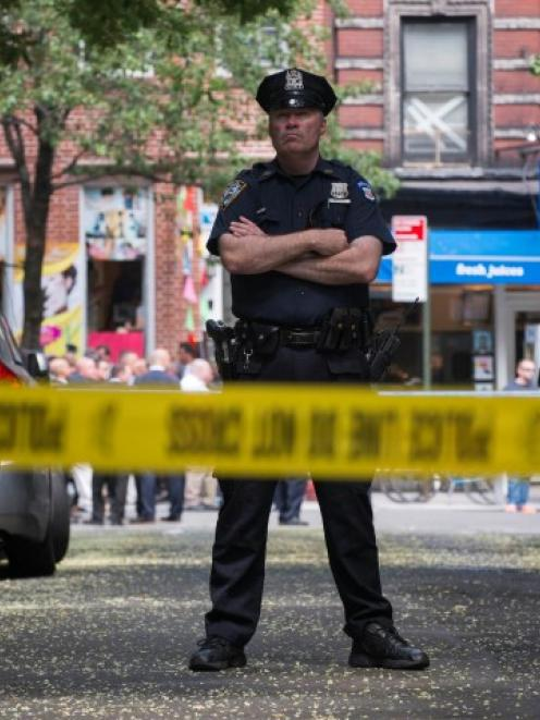A New York Police Officer stands guard inside a cordoned area at the site of a shooting in...