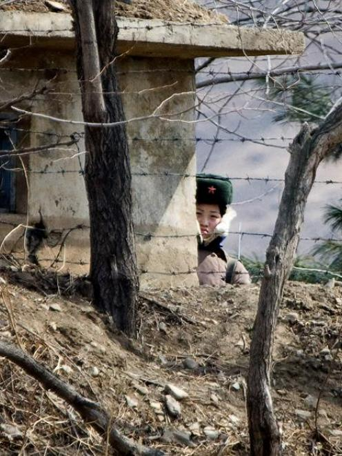 A North Korean female soldier stands watch at the waterfront of the Yalu River at the North...