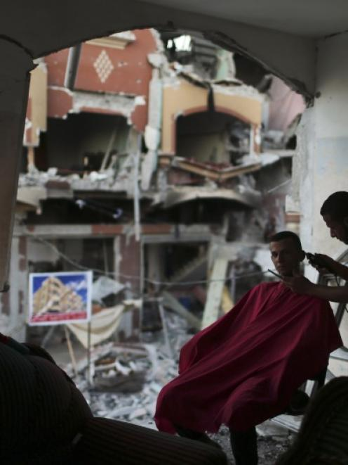 A Palestinian barber cuts a man's hair at the remains of his house, which witnesses said was...
