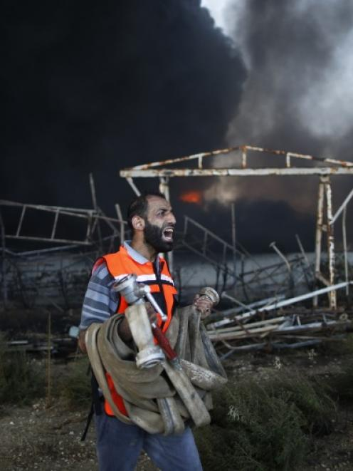 A Palestinian firefighter reacts as he tries to put out a fire at Gaza's main power plant, which...