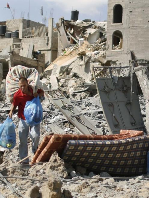 A Palestinian man carries his belongings from his destroyed house in Beit Hanoun town, which...