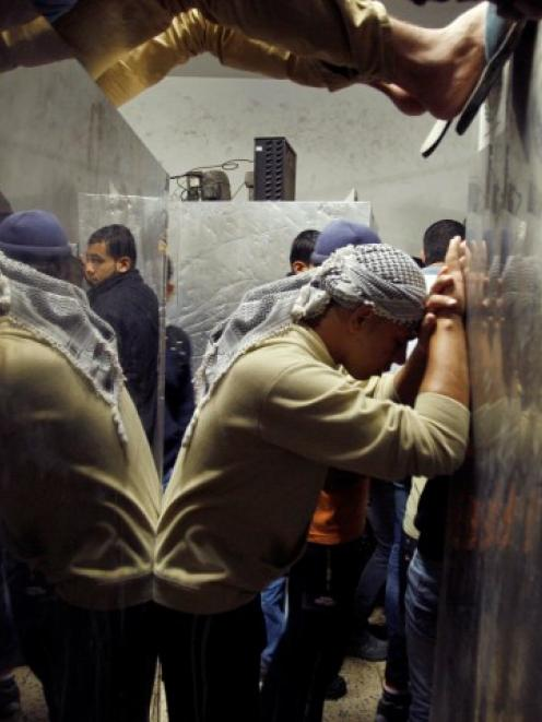 A Palestinian man is reflected in a hospital morgue as he reacts to the death of a relative in an...