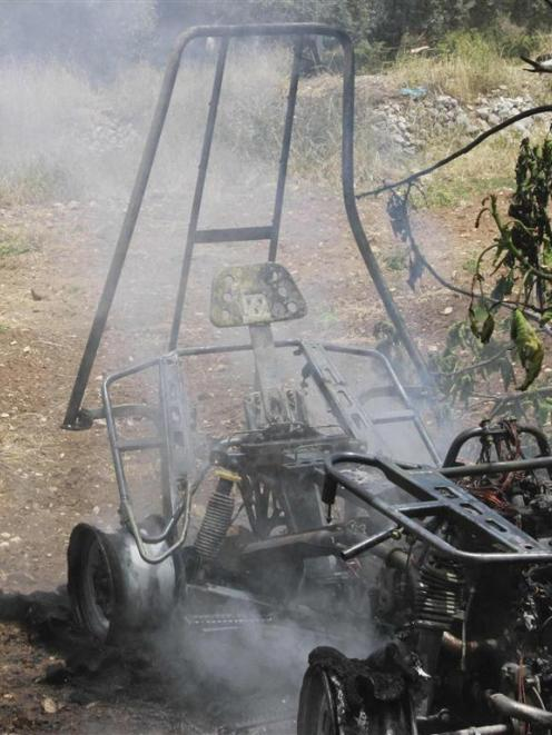 A Palestinian man looks at the remains of a quadbike set on fire by Palestinians after it was...