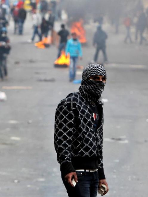 A Palestinian protester holds stones during clashes with Israeli soldiers in the West Bank city...