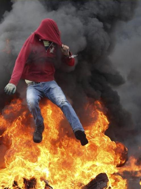 A Palestinian protester jumps over burning tyres during clashes with Israeli troops near the...