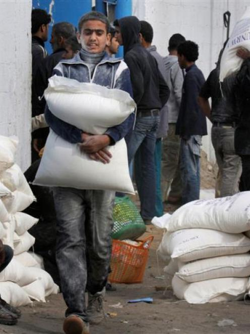 A Palestinian youth carries flour after he received it at a United Nations food distribution...