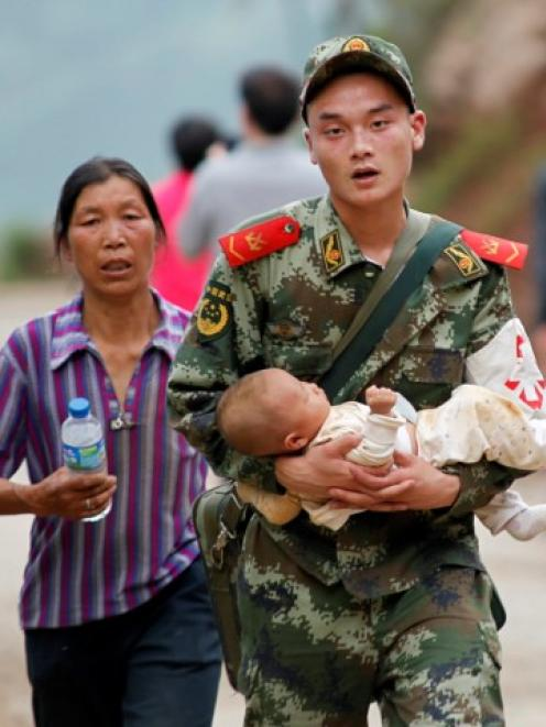 A paramilitary policeman carries a baby as resident vacate the earthquake area. REUTERS/China Daily