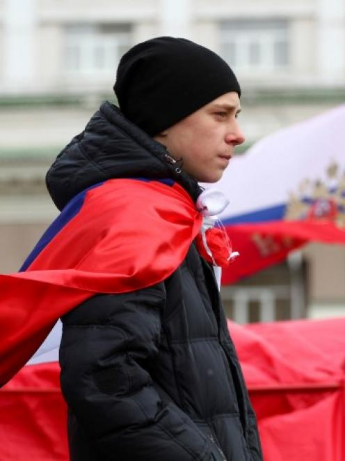 A participant wears a Russian flag during a pro-Russian rally outside the regional administration...