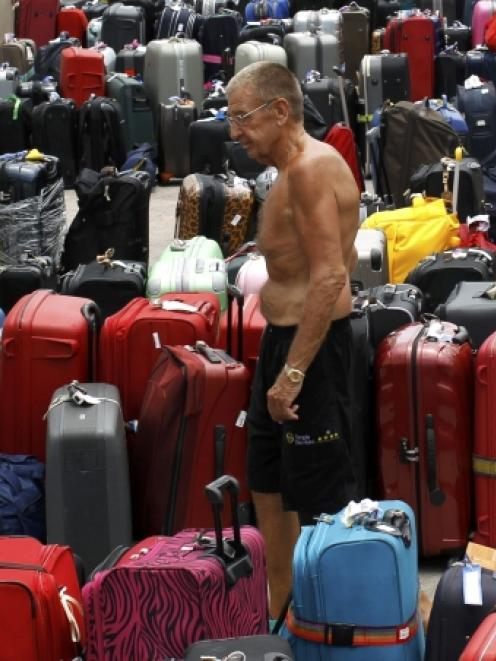 A passenger looks for his bags after alighting from the Costa Allegra cruise ship at Mahe port in...