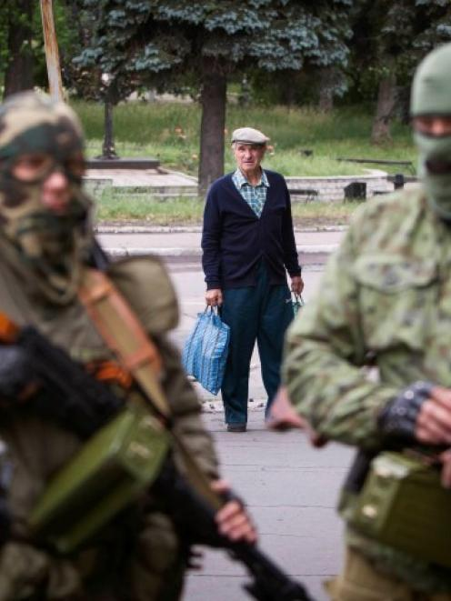 A passer-by stops to look at armed pro-Russian separatists at a town centre in Snizhnye in...