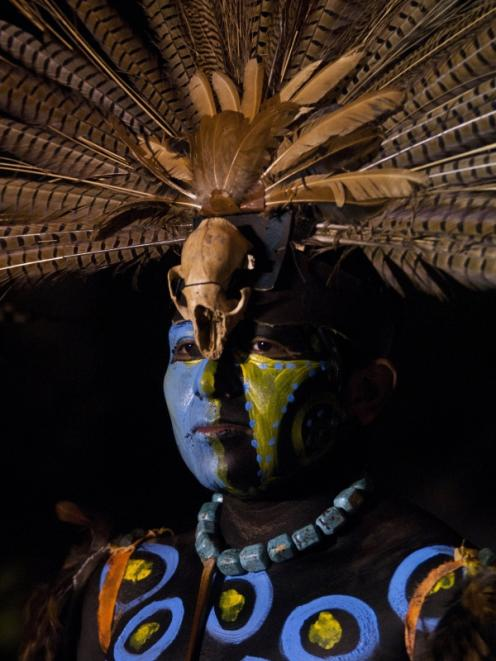 A performer wears a traditional costume as he takes part in the opening ceremony of the Mayan...