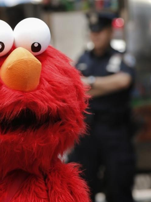A person dressed as the Sesame Street character Elmo walks through Times Square in New York....