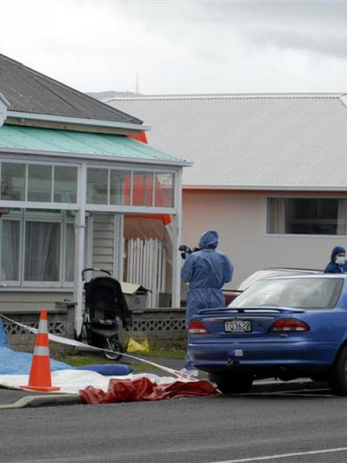 A photographer studies a child's buggy as ESR scientists and police examine the scene of a fatal...
