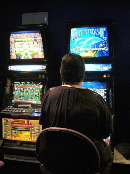 A pokie player  generates cash. Photo by Jane Dawber.