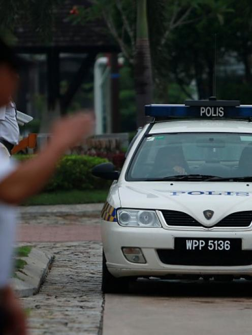 A police car exits the compound of the home of pilot Zaharie Ahmad Shah, the captain of Malaysia...