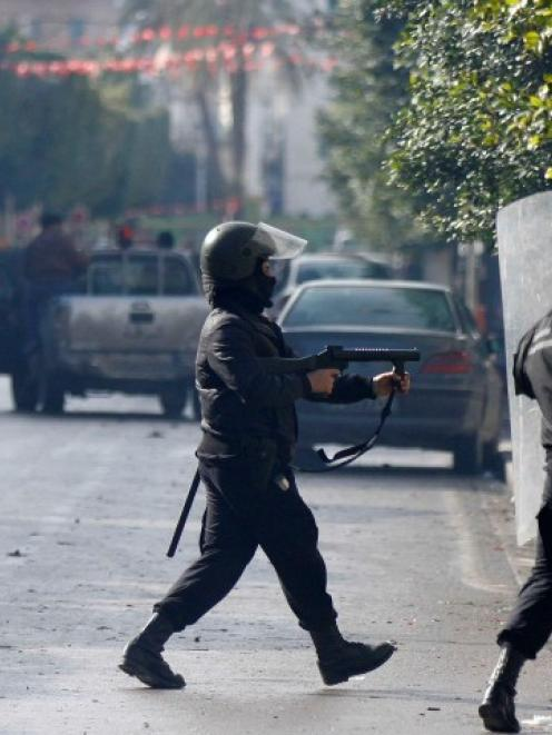 A police officer fires teargas to break up a protest during a demonstration near the Interior...