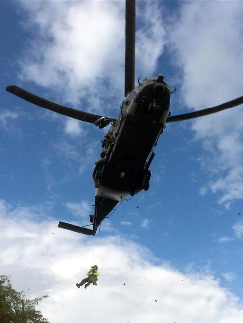 A police officer  hangs beneath an RNZAF NH90 during a cannabis recovery operation over Westwood...