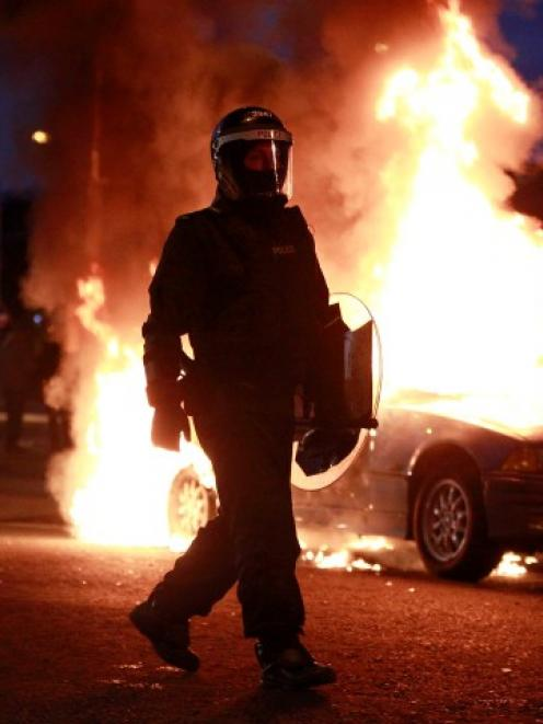 A police officer in riot gear walks past a burning hijacked car during rioting in East Belfast....