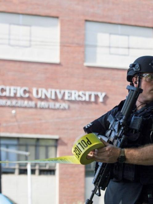 A policeman helps secure the scene at Seattle Pacific University after the campus was evacuated...