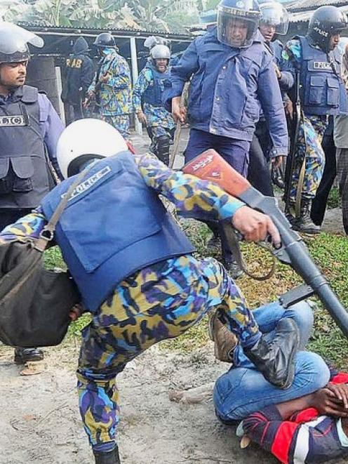 A policeman kicks a protester during a clash after protesters attacked and set fire to polling...