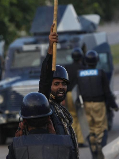 A policeman raises his stick as he calls for fellow policemen to disperse anti-government...