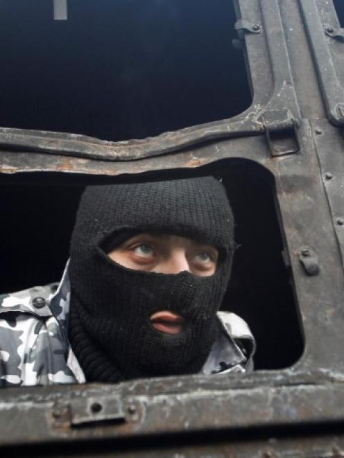 A Pro-European integration protester look out of a burnt police truck at the site of clashes with...