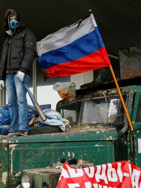 A pro-Russia protester stands at a barricade outside a regional government building in Donetsk,...