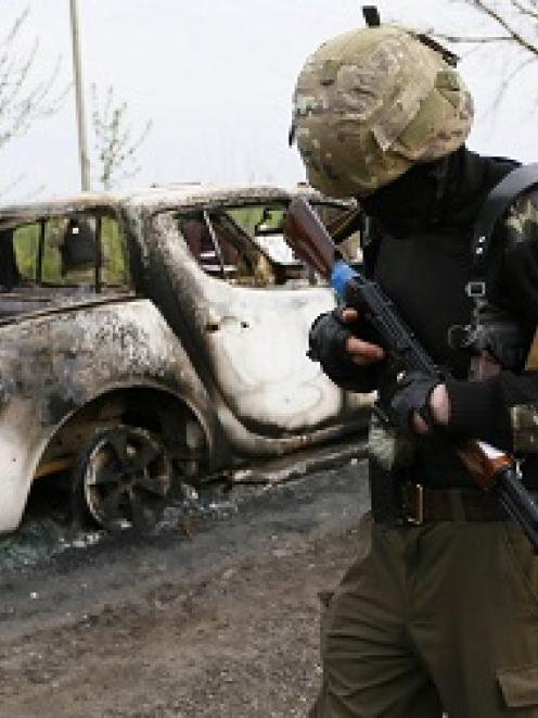 A Pro-Russian militant walks past burnt cars near a checkpoint that was the scene of a deadly...
