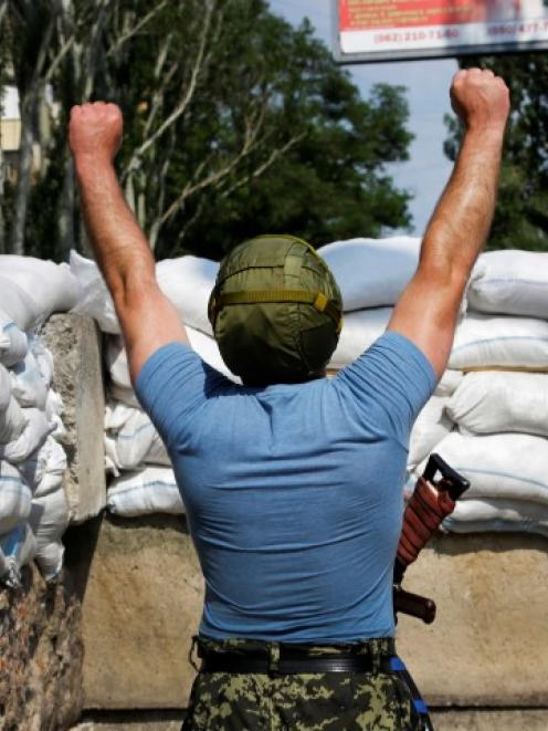 A pro-Russian rebel stretches while manning a barricade near the Ukrainian Security Service in...